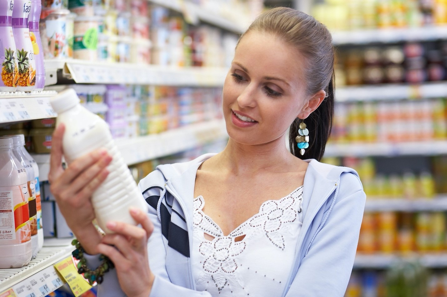 Woman in supermarket looking at the ingredients on a bottle