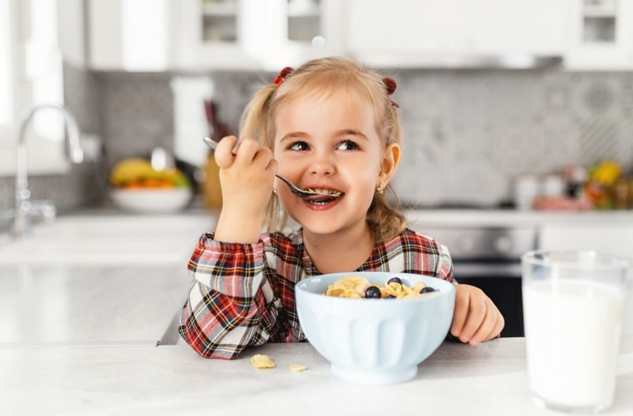 Little girl eating a bowl of cereal